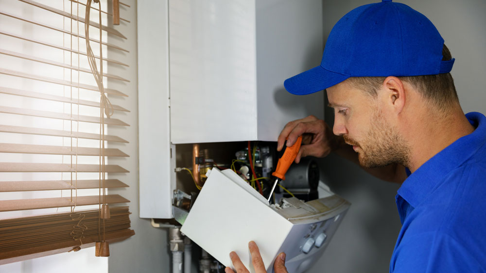 Gas engineer servicing boiler
